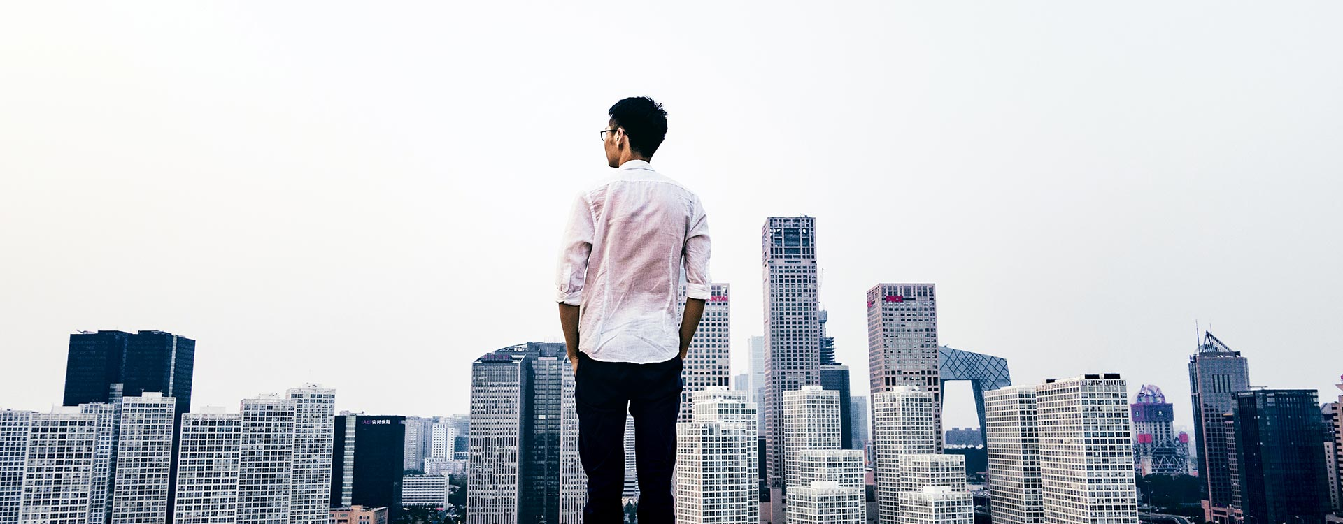 Male Professional Looking Out over City Landscape