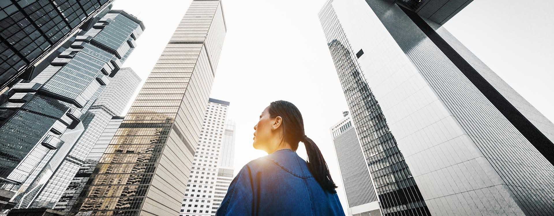 Female Professional Looking up at City Buildings