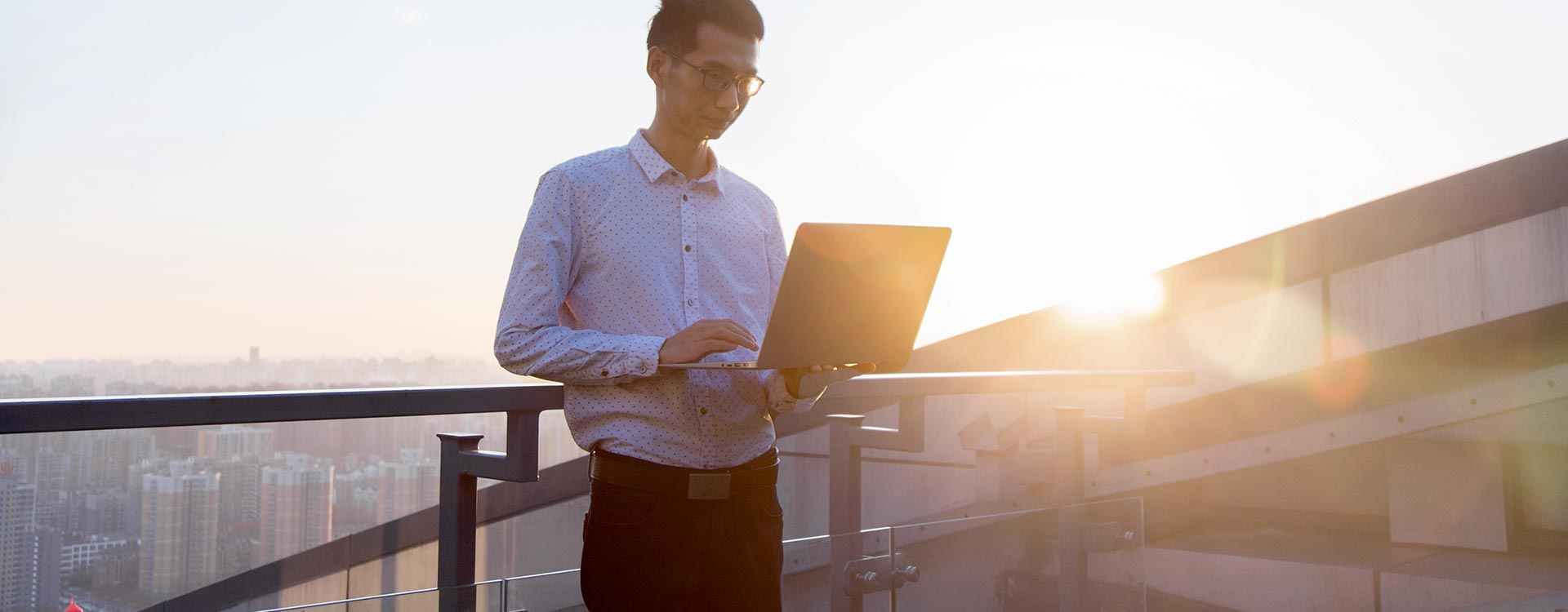 Male Professional Working at Laptop PC on Rooftop