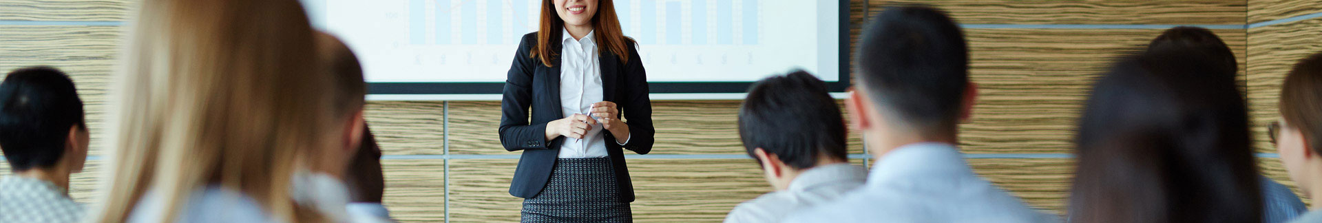 Smiling instructor presenting to executives