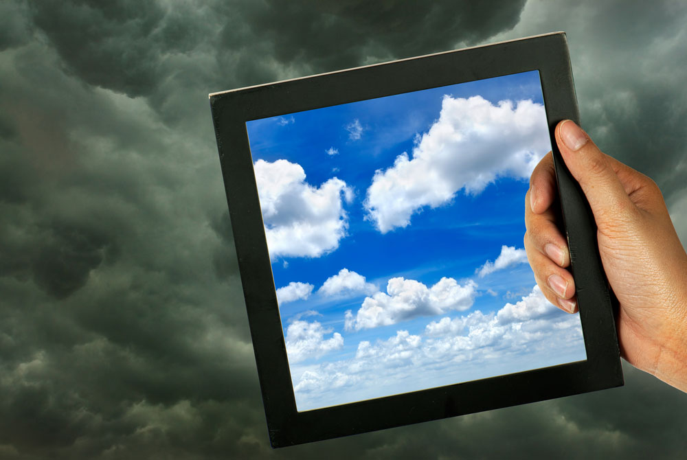 Hand holding a frame of blue sky and clouds against a stormcloud background